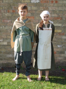 A boy wears a traditional long shirt and cloak, while a girl wears an apron dress and headscarf. Image links to www.historyoffthepeg.co.uk