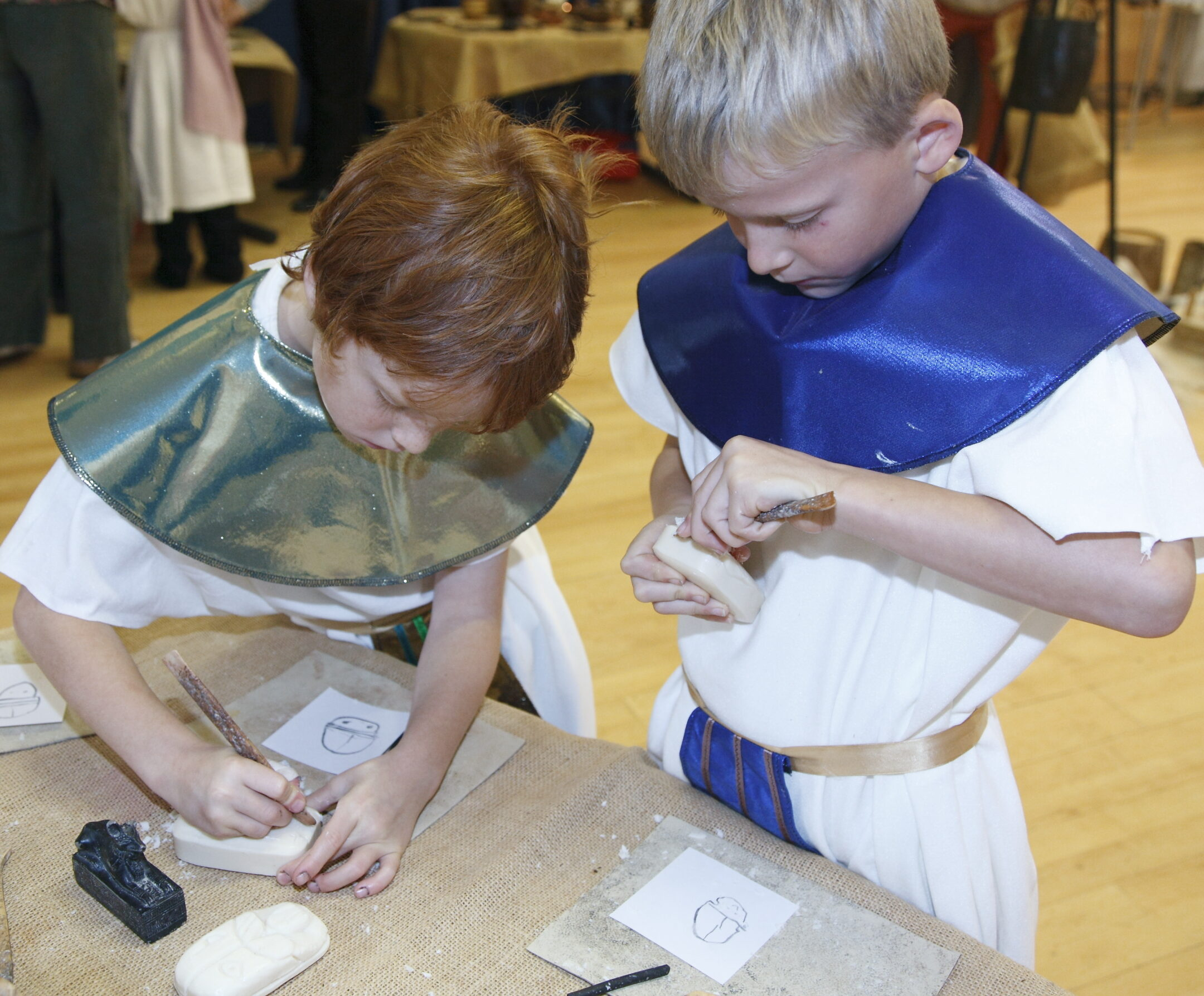 Two boys use wooden sticks to carve figures into white bars of soap.