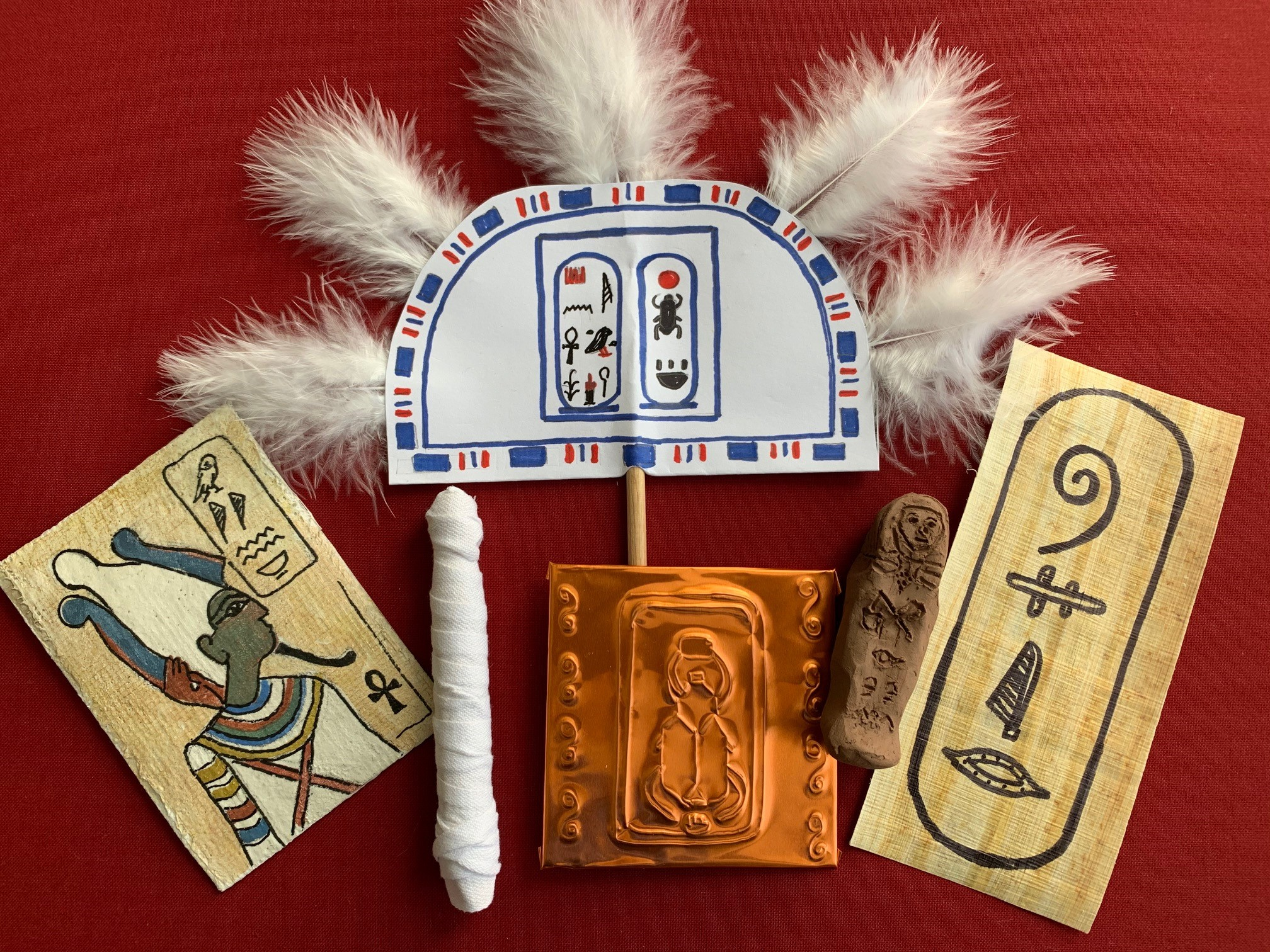 The items include a tomb painting, a mummified doll, an engraved plaque made with golden foil, a feather fan, a clay shabti doll and a papyrus cartouche.