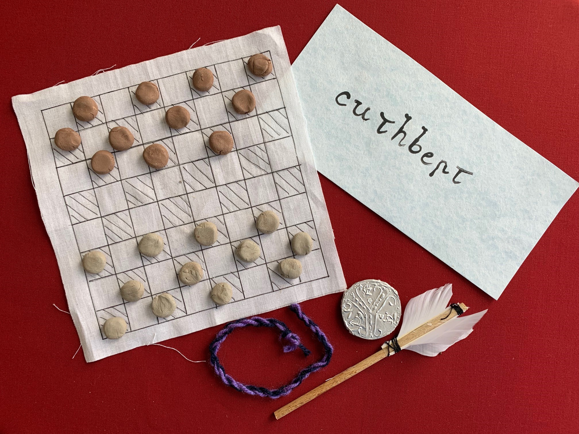 The items displayed include a draughts board, a handwriting sample, a fletched arrow, a silver coin and a woolen braid.