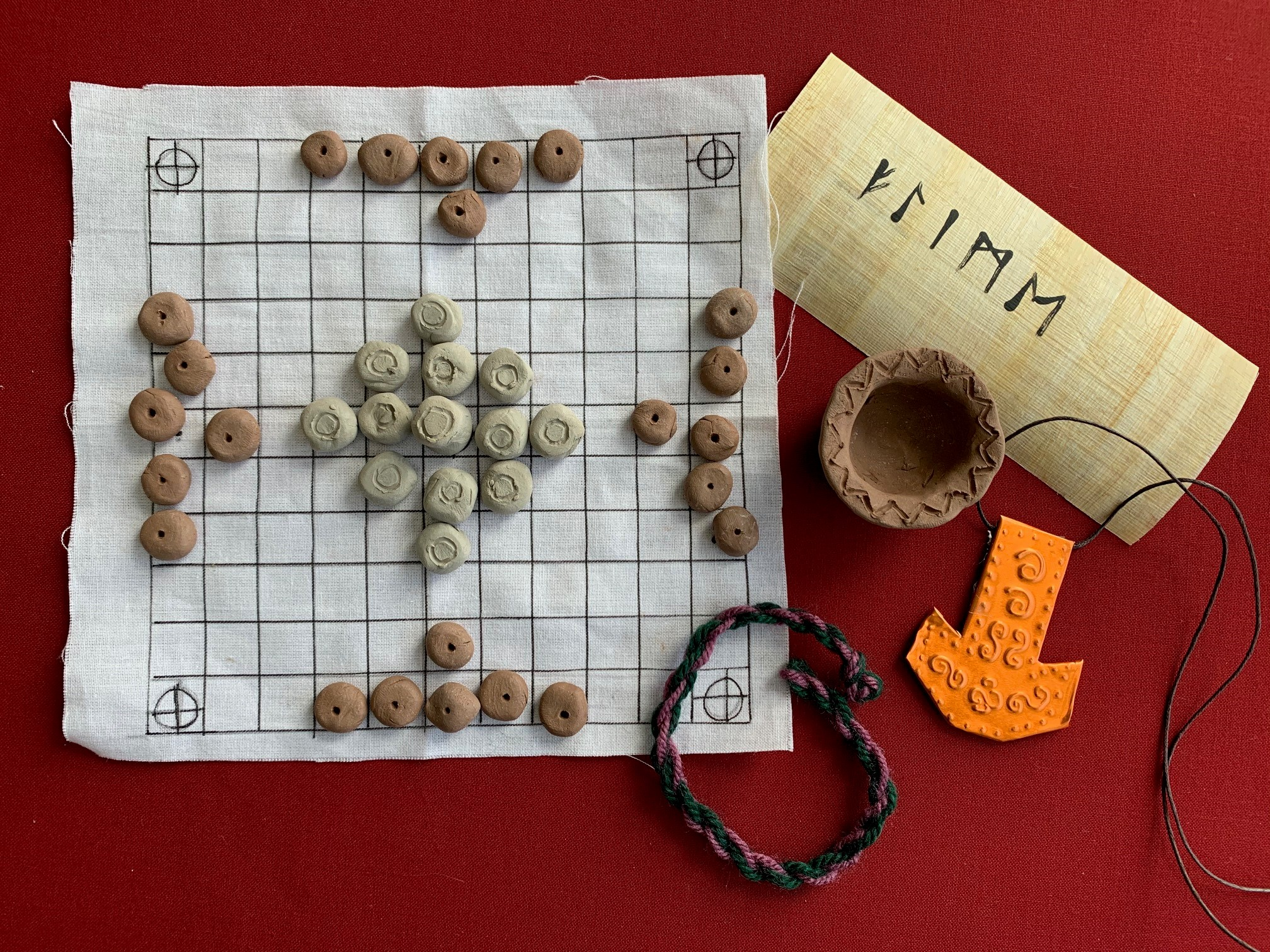 The projects include a hnefatafl game set, a writing sample in runes, a clay pot, a Thor's hammer amulet and a woolen braid.