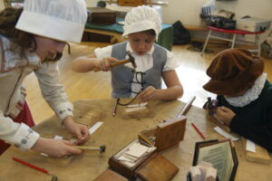 The children are dressed in Tudor clothing and use small hammers to tap patterns into leather during our KS2 Tudor workshop.