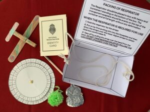The items include a cipher wheel, a toy plane made with a clothes pin, a dip pen and National ID card, a paper gas mask box with string, a foil ARP badge and a yarn bobble.