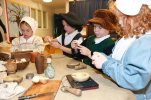 Children dressed as 17th-century Londoners work with herbs, mortars and pestles.