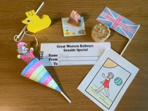 The items include a paper puppet in a cone, a yellow hook a duck game, a cork ship on a paper base, a Union Jack flag, a coloured paper postcard and a train ticket.