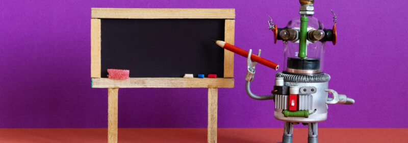 A toy robot points to a blackboard.