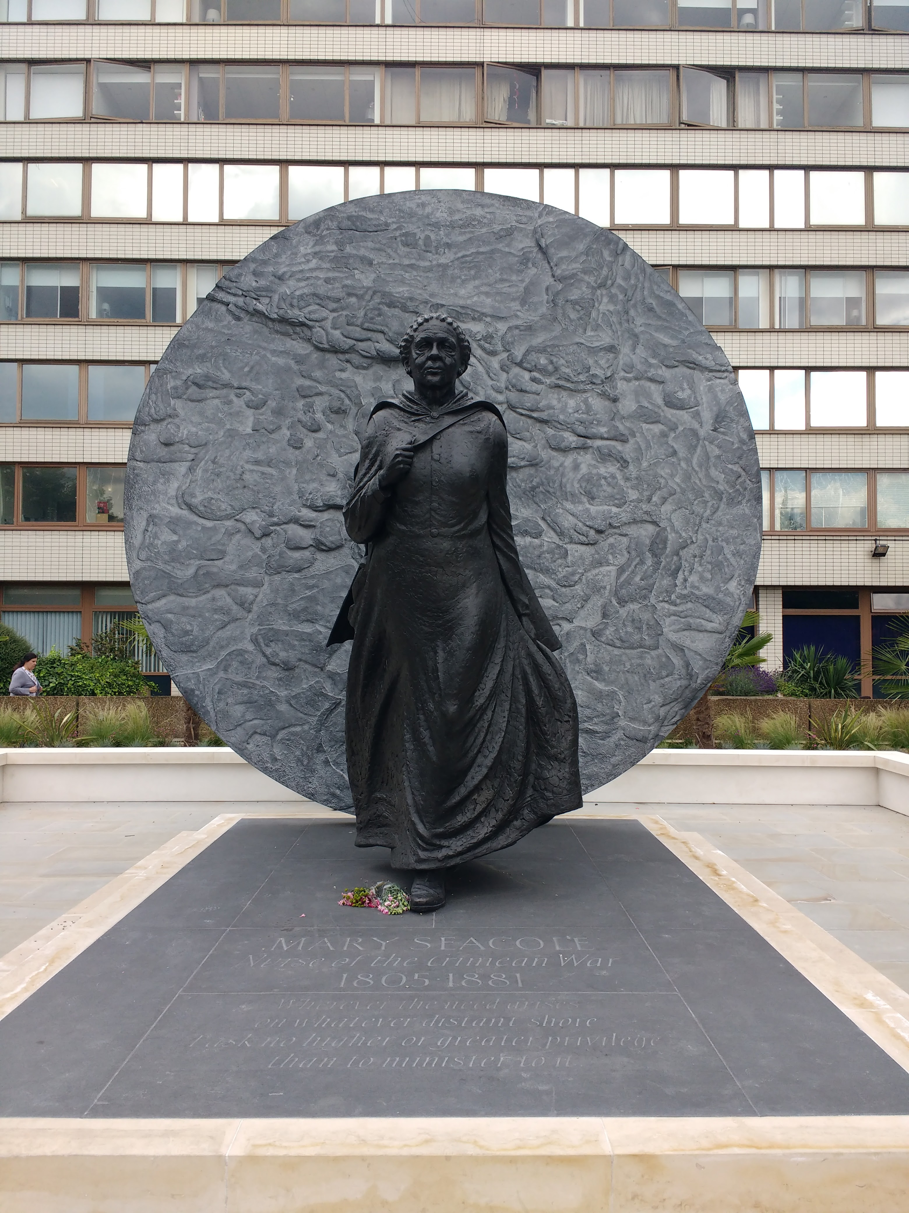 The statue depicts Mary walking forward in a long dress, with a circle behind her.