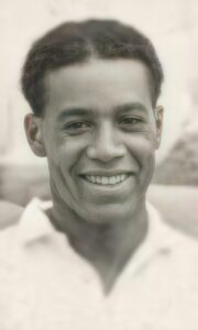 A detailed, modern-style headshot of Walter Tull that shows a dimpled smile and light freckles on his face.