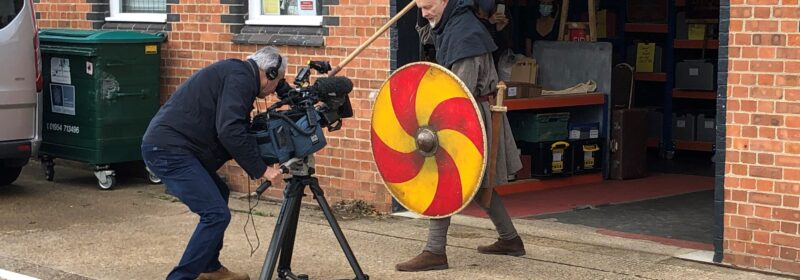 The video camera gets a close up of a man menacing looking man brandishing a spear and shield.