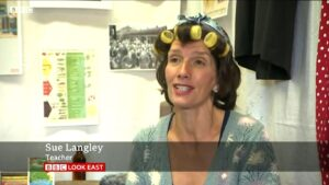 A woman in an old-fashioned jumper and hair curlers speaks in a small studio filled with Second World War artefacts.