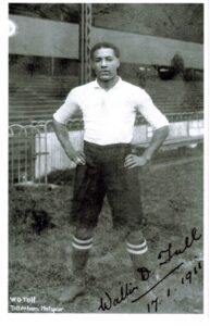 Walter -- in white shirt and black shorts with striped socks -- stands with hands on hips. A signature in the corner is dated 1911.