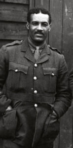 Walter Tull stands with his hands in the pockets of his Army uniform.