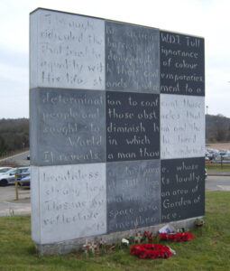 The memorial consists of a large patchwork of grey stones with script on the surface. Poppy wreaths lie at the base.