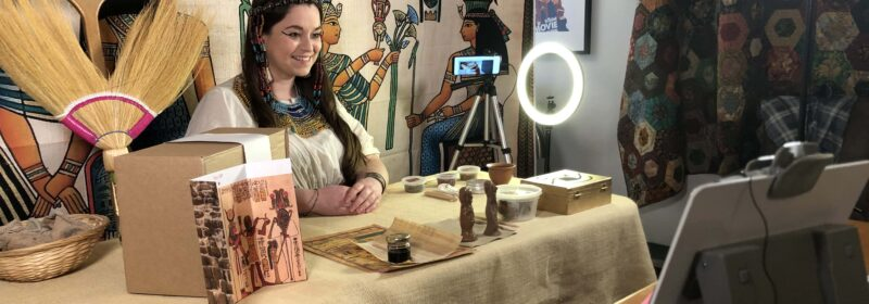 Vicky is dressed as an Ancient Egyptian. She has hieroglyphs behind her, artefacts in front of her, and cameras and lights surrounding her in this behind-the-scenes shot.
