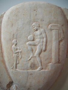 A carving shows a young man balancing a ball on his knee, much like modern football players.