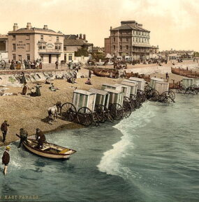 An old postcard image shows waves lapping against a smal boat and several wheeled carts that were used to carry bathers into the water.