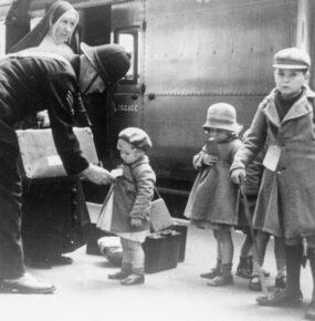 Three children with tags around their neck stand on a train platform looking bewildered.